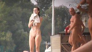 Sun warming up bodies of beach nudist girls and men